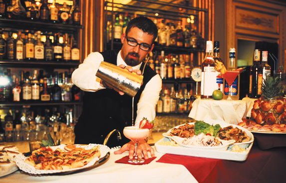Aperitivo in Turin - Barman serving drinks with food out on bar which is called apericena (a drink and some food to nibble on)