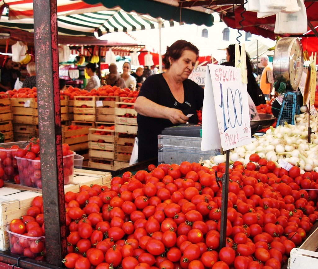 shopping in turin - image of female vendor selling tomatoes at Turin's local food market