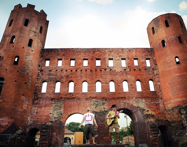 two band members playing in front of the old roman gate of turin