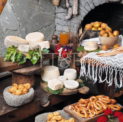 a rustic setting with food layout consisting of breads, cheeses and pears