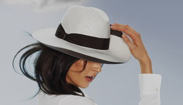 Female model wearing a white Borsalino hat made in Piedmont