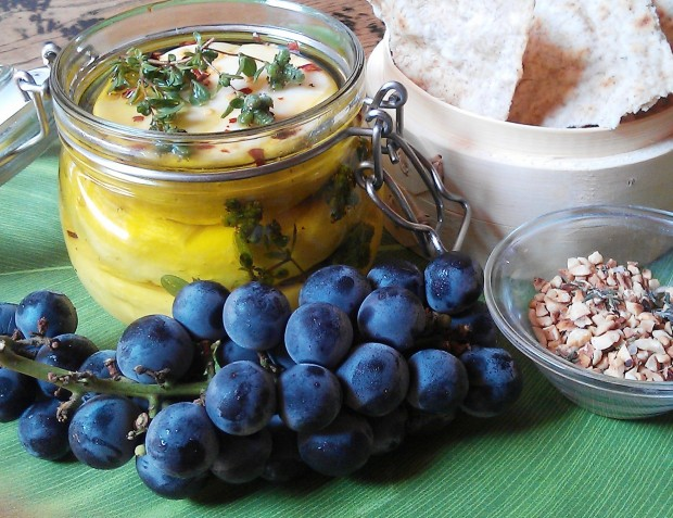 cup of cheese with herbs and bunch of grapes