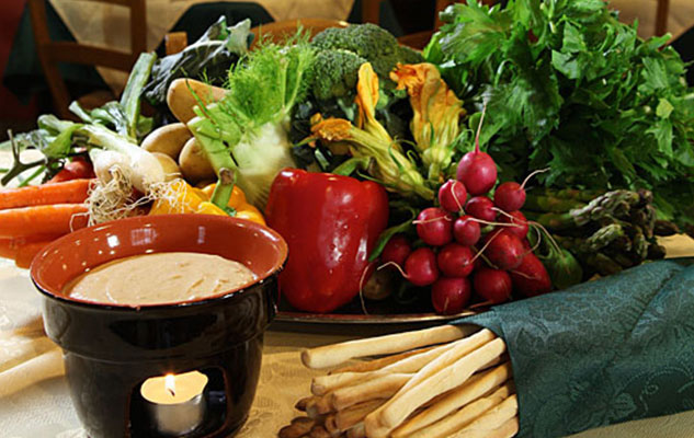 foodies guide to piedmont - Bagna Cauda with a plate of veggies and breadsticks set up on a table