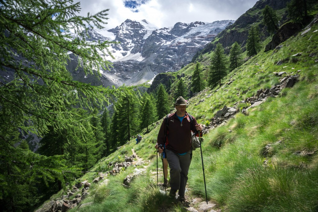 couple trekking in open field with mountains in Gran Paradiso National Park