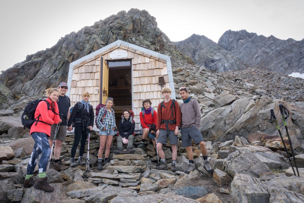 hikers posing in front of a small mountain hut in Gran Paradiso National Park