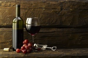 Cari wine photo of red wine with rustic wood wall in backdrip with grapes and wine bottle opener