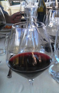 Barolo wine glass with red wine in it at table