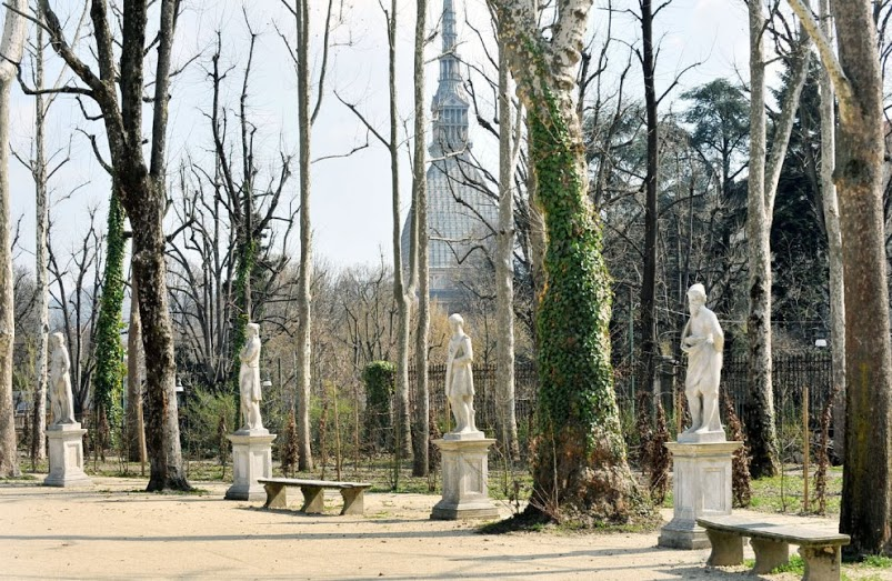 Turin's Royal Gardens with white statues in garden and Mole in the background