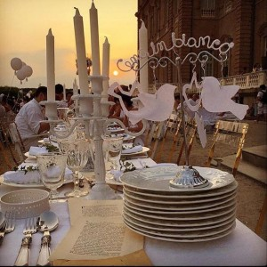 Cena in Bianco elegant table setting with white linens candles plates and ballons