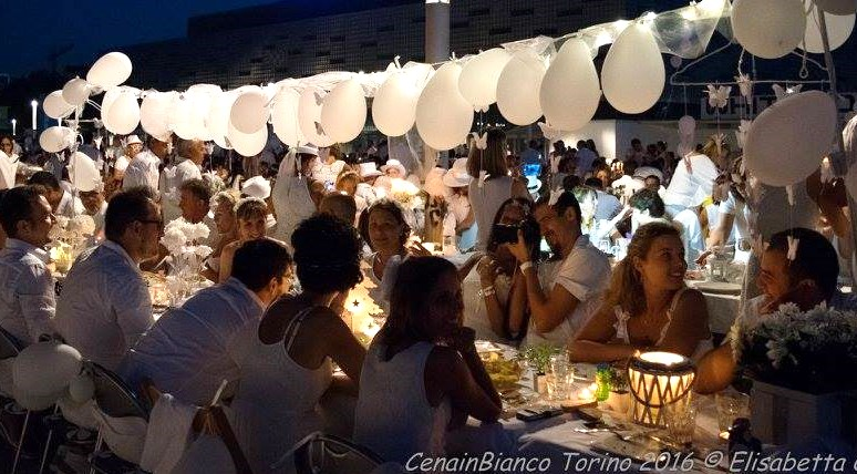 Cena in Bianco participants dressed in white sitting at long table adorned in balloons and candles