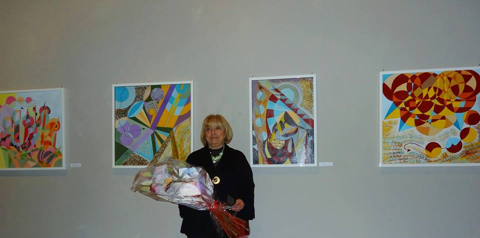 Lea Ricci Turin Artist in front of her paintings at an art exhibit in Turin