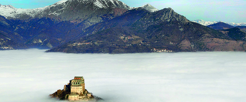 things to see in piedmont - the Sacra di San Michele exterior with view of mountains and covered in clouds