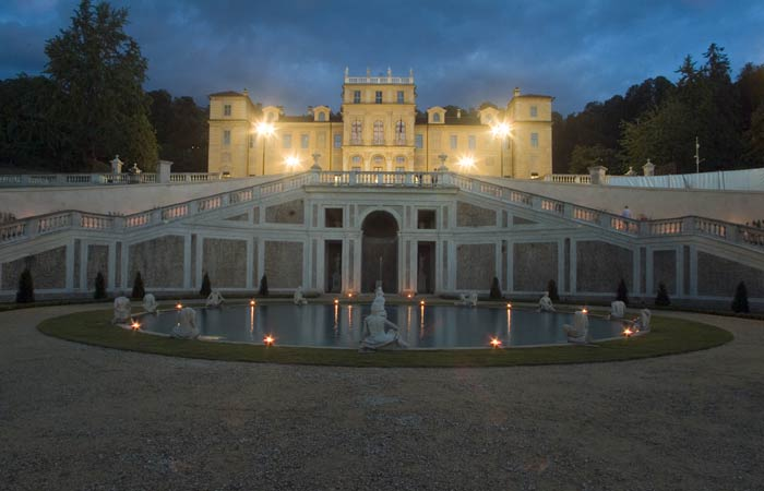 An attraction to visit in Turin is Villa della Regina. Image is of Villa della Regina by night with fountains in the front of the facade