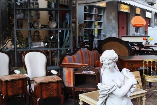 Antique furniture and statues displayed outside antique shop at Turin Balon market