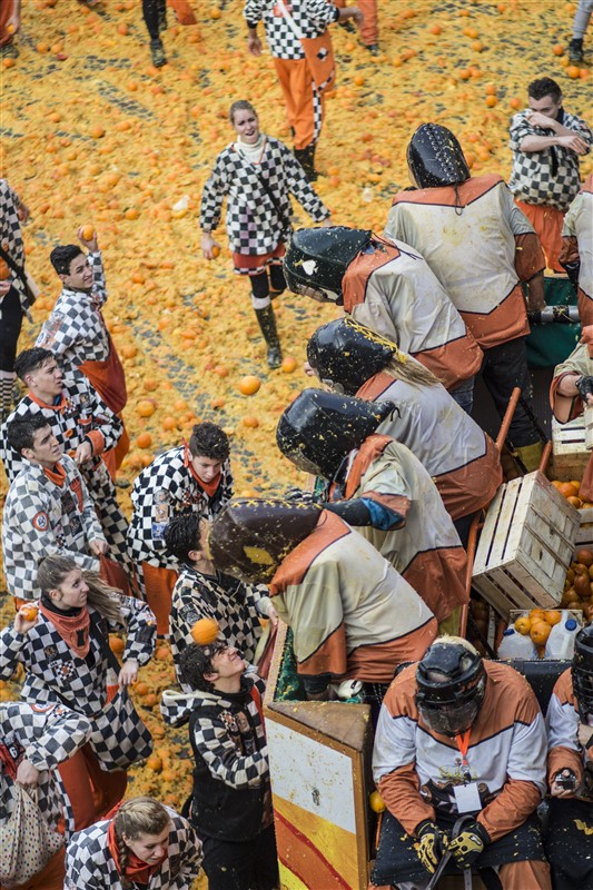 crowd of people throwing oranges at each other during the battle of oranges