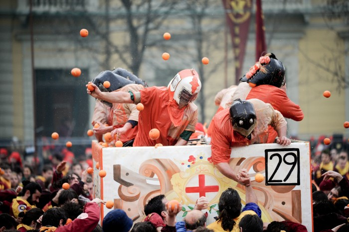 Crowd throwing oranges during the battle of oranges in Ivrea