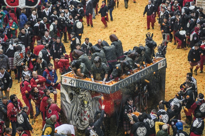Ivrea Battle of Oranges fight scene with people throwing oranges and the streets covered in a sea of orange