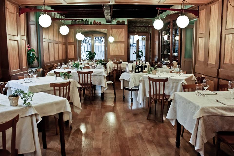 Where to Eat Like a Local In Turin - the Tre Galline restaurant interior with wood tables and chairs
