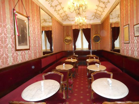 cafes & bars in turin - this is the historic Caffe Fiorio interior with red velvet carpet, tapestry walls and small marble tables