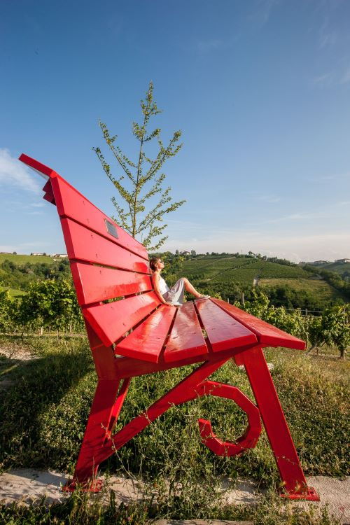 Big Benches in Piedmont in red with lady sitting on it taking sun within the vineyards